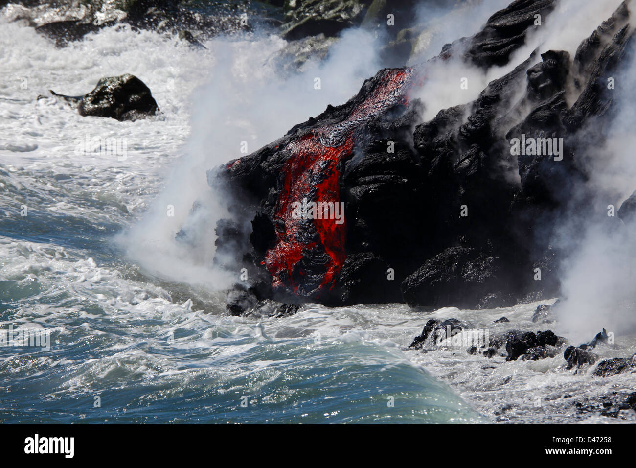 The Pahoehoe lava flowing from Kilauea has reached the Pacific ocean near Kalapana, Big Island, Hawaii. Stock Photo