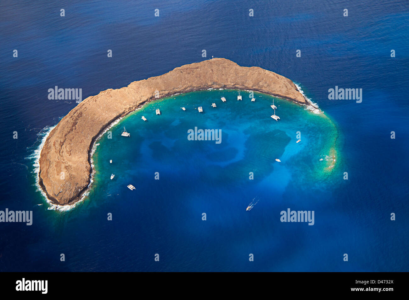 Molokini Crater, aerial shot of the crescent shaped islet at mid-morning with charter boats, Maui, Hawaii. - Stock Image