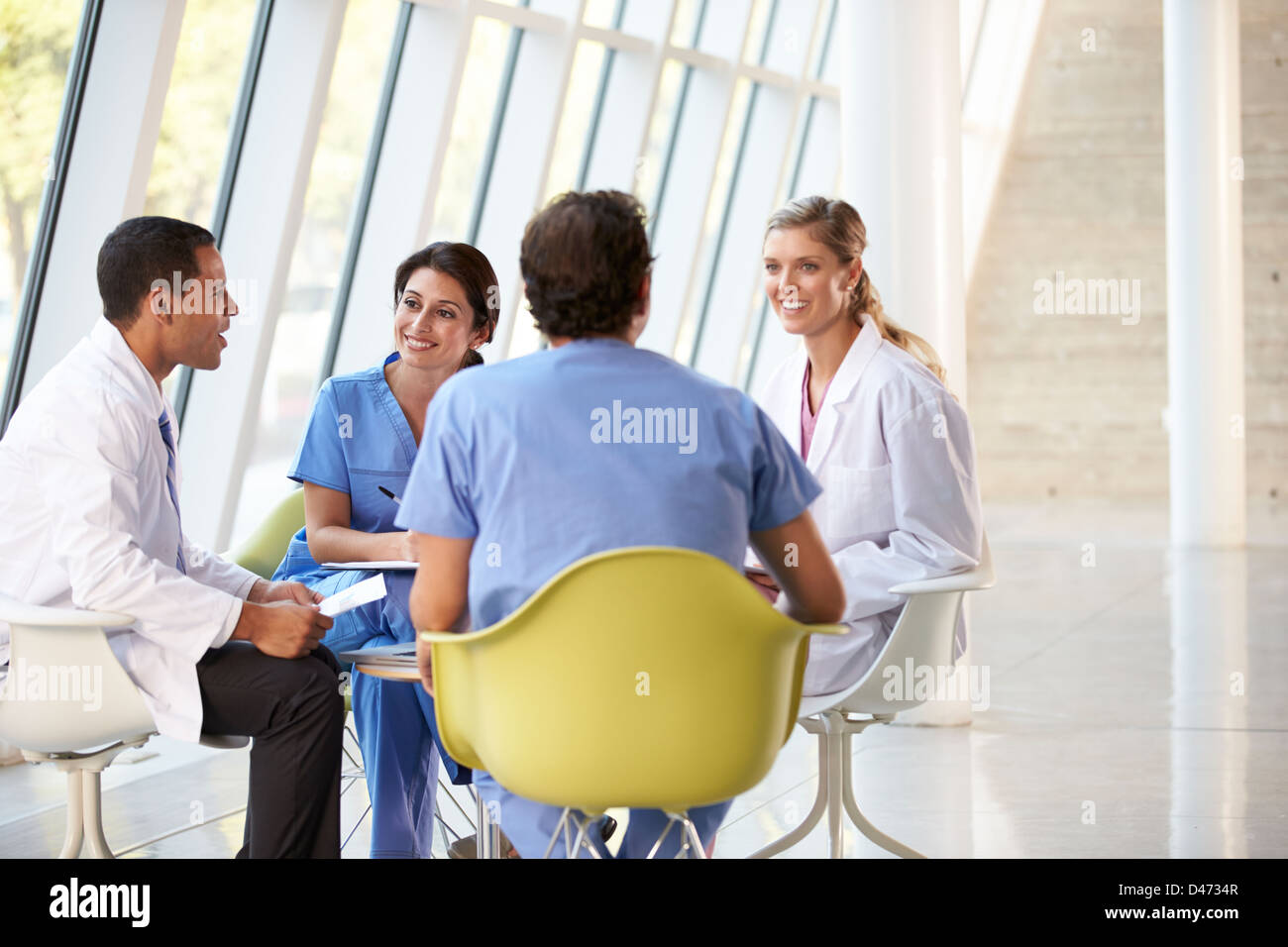 Medical Team Meeting Around Table In Modern Hospital - Stock Image