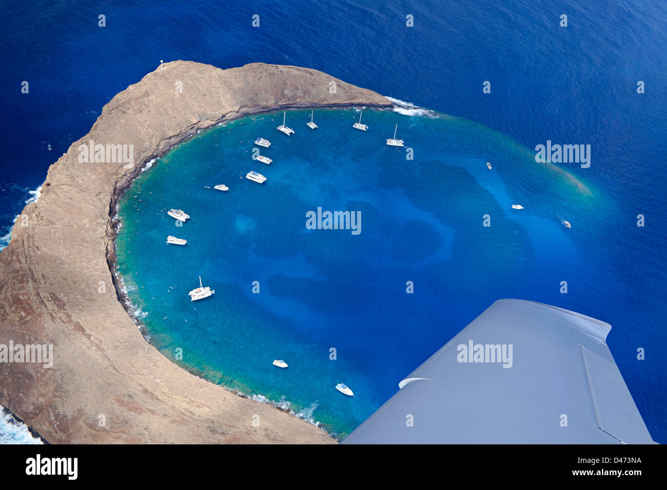 An aerial look out the window from a small plane at Molokini Crater, at mid-morning with charter boats, Maui, Hawaii. - Stock Image