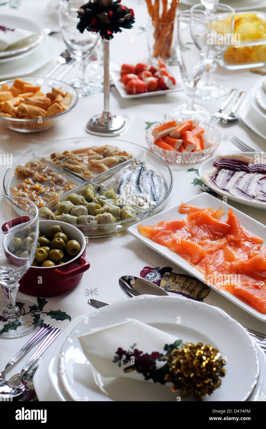 Christmas laid table appetizer snack aperitif  olives cockles artichokes, napkin,  cups, - Stock Image