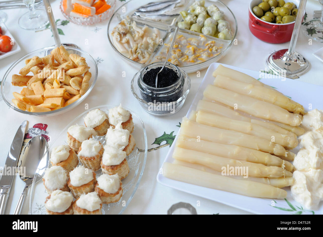 Christmas laid table appetizer snack aperitif  olives cockles artichokes, vol au vent with cod asparagus with mayonnaise, - Stock Image