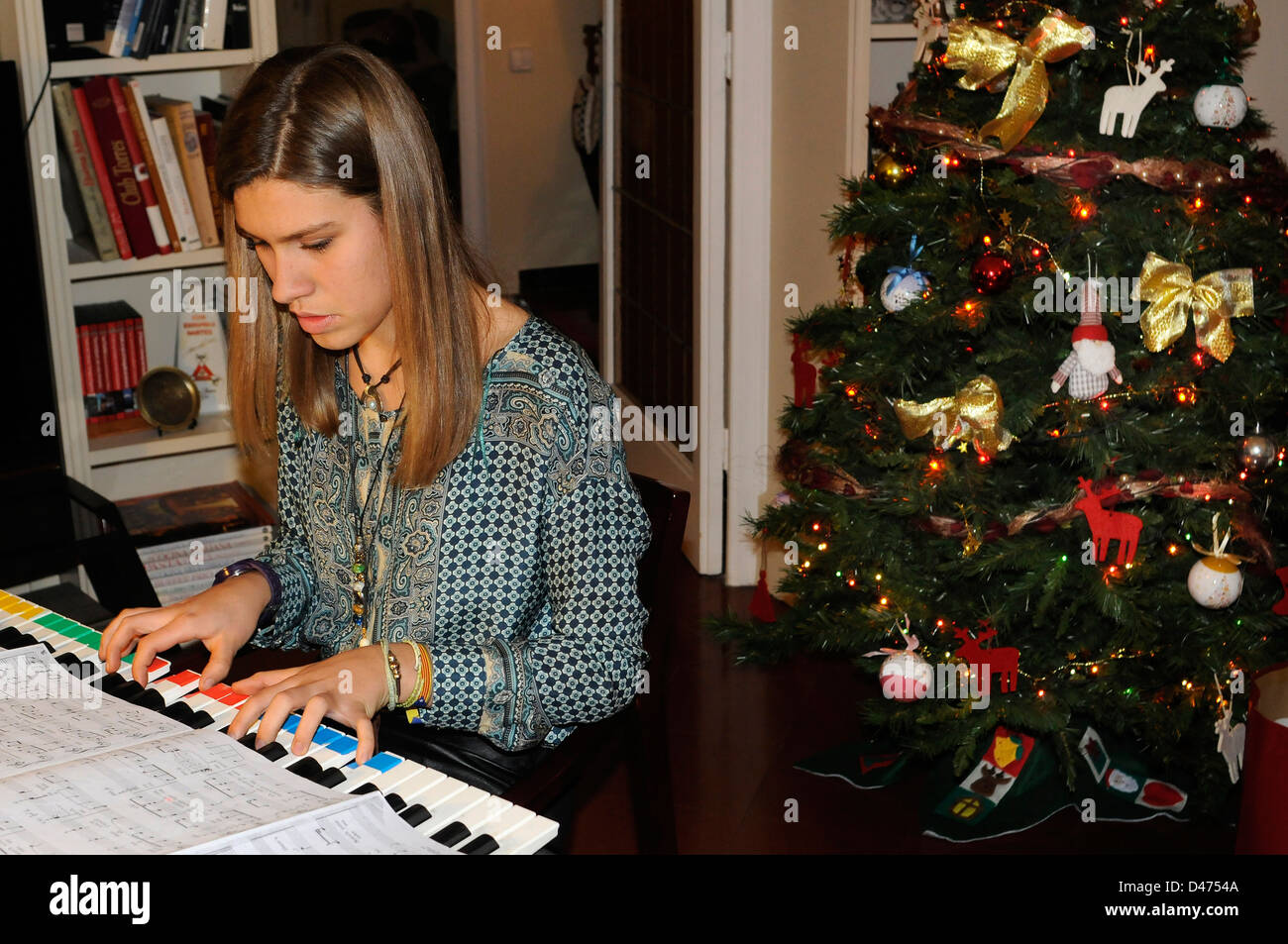 Young lady playing electric piano at home on Christmas week, Christmas tree on the background - Stock Image