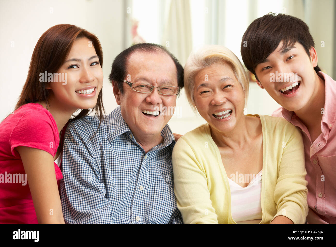 Portrait Of Chinese Parents With Adult Children Relaxing At Home Together - Stock Image