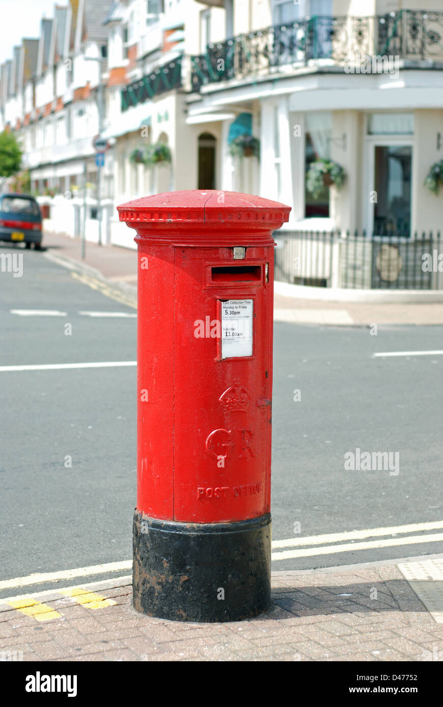 red British mail box on a city street - Stock Image