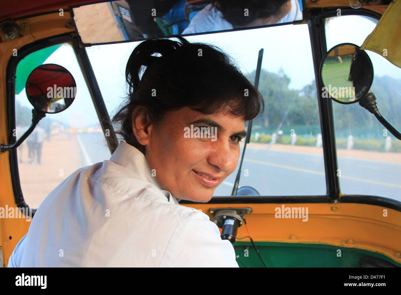 Rickshaw driver Sunita Chaudhry sits in her vehicle and smiles on a