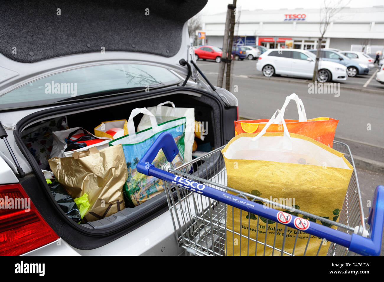 Shopping bags in a Tesco shopping trolley and car boot in a Tesco car park, Scotland, UK - Stock Image