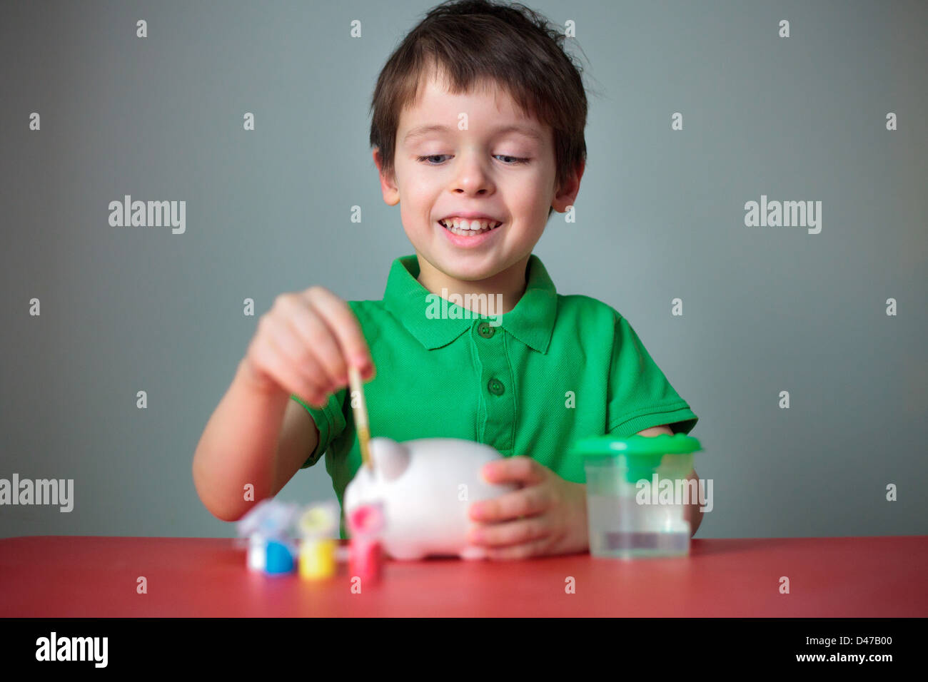 Cute happy little boy painting his piggy toy - Stock Image