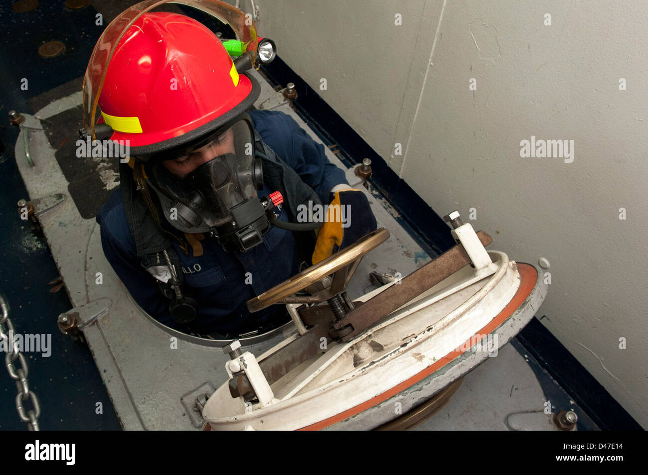 A Sailor enters a space during a toxic gas damage control drill. - Stock Image