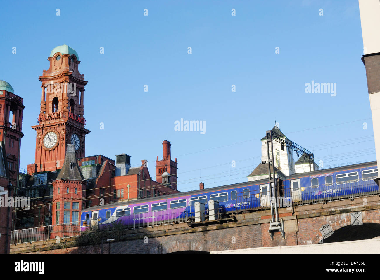 Commuter train passing through Manchester city centre by Oxford Road with the Refuge Building in the background. - Stock Image