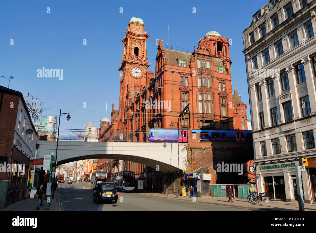 Oxford Road in Manchester showing the Refuge building and railway bridge at Oxford Road railway station. - Stock Image