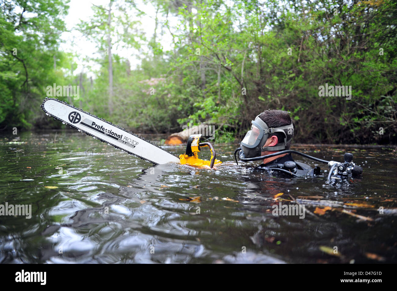 An Underwater Construction Team member hands off their hydraulic saw in preparation to exit the river during a field Stock Photo