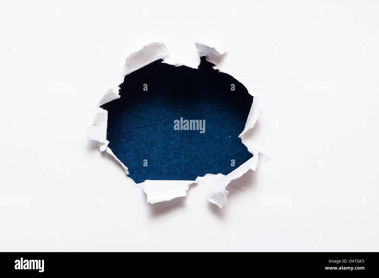 Breakthrough paper hole with black textured background. - Stock Image