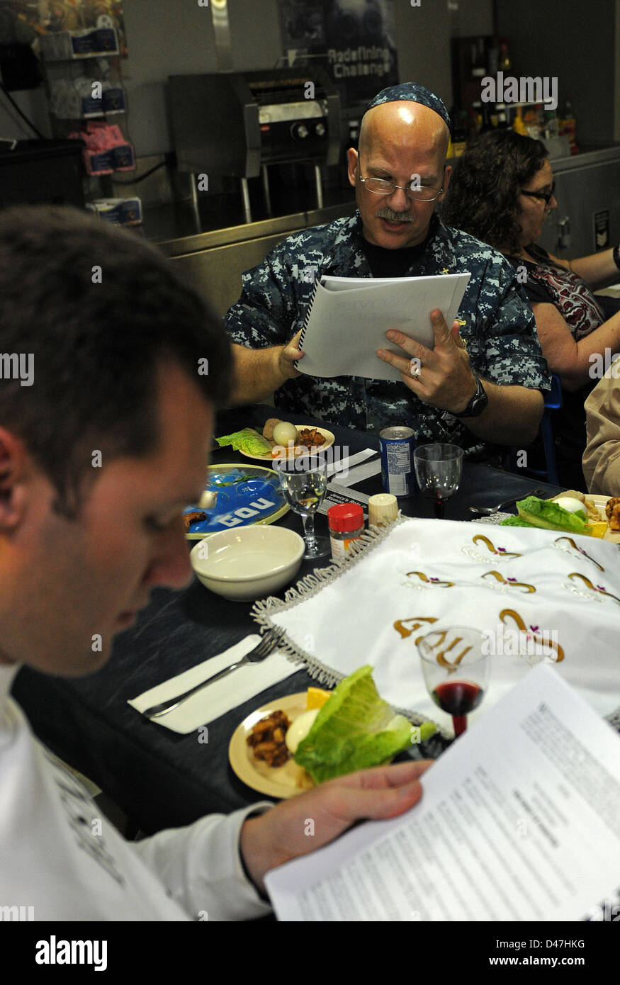 Sailors conduct a Siddur during a Passover ceremony. - Stock Image