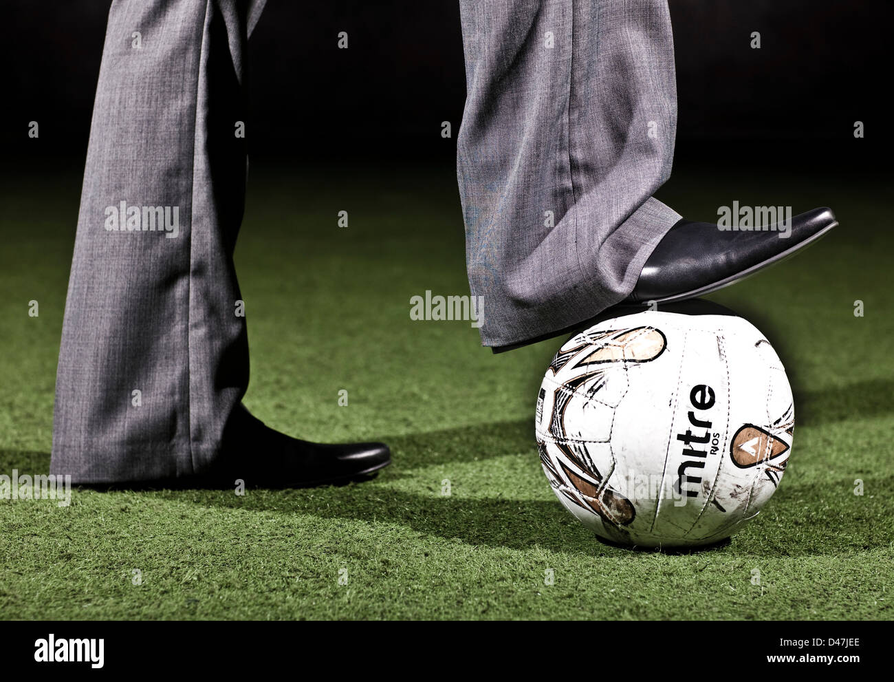 Footballer resting foot on ball - Stock Image