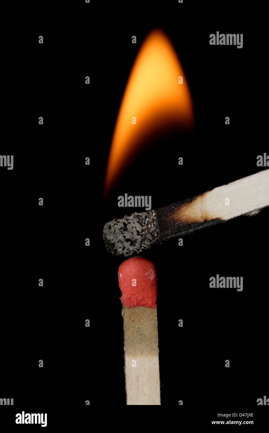 Burning match  resting on top of unlit match prior to ignition. - Stock Image