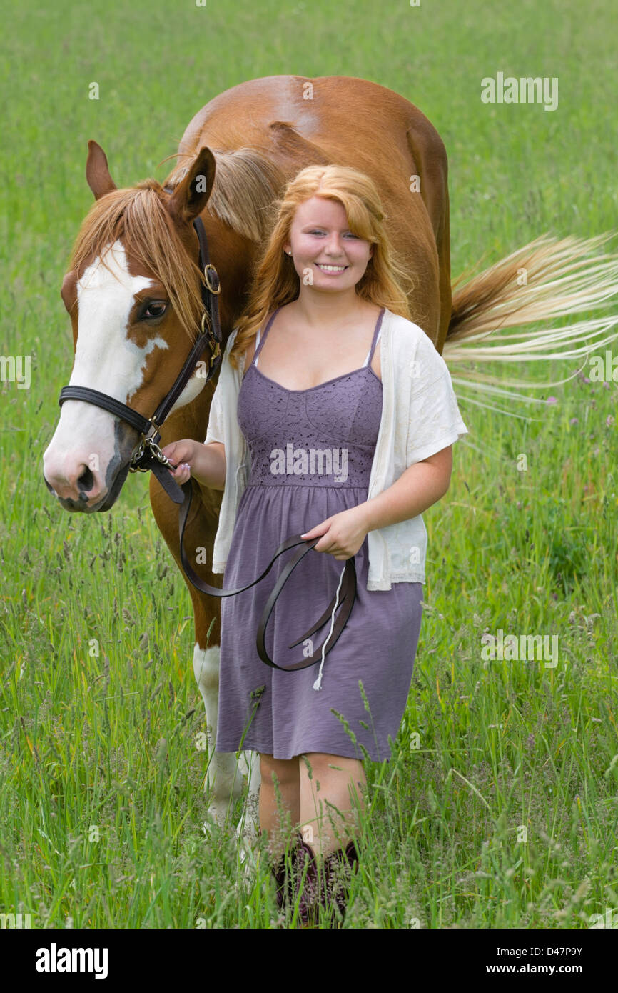 Young woman leading horse through grassy field, an eighteen year old red haired horsewoman. - Stock Image