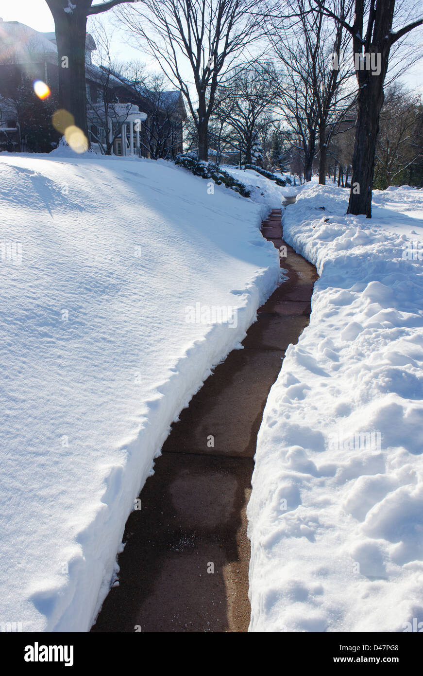 Long snowy path in a residential neighborhood. - Stock Image