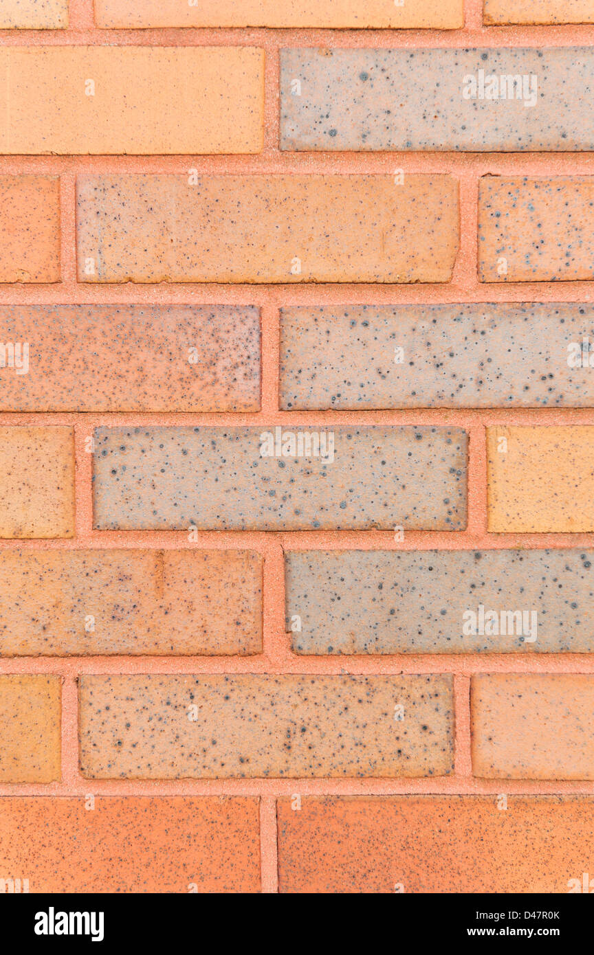 Brick wall background in orange and  red for a design element, close up. - Stock Image