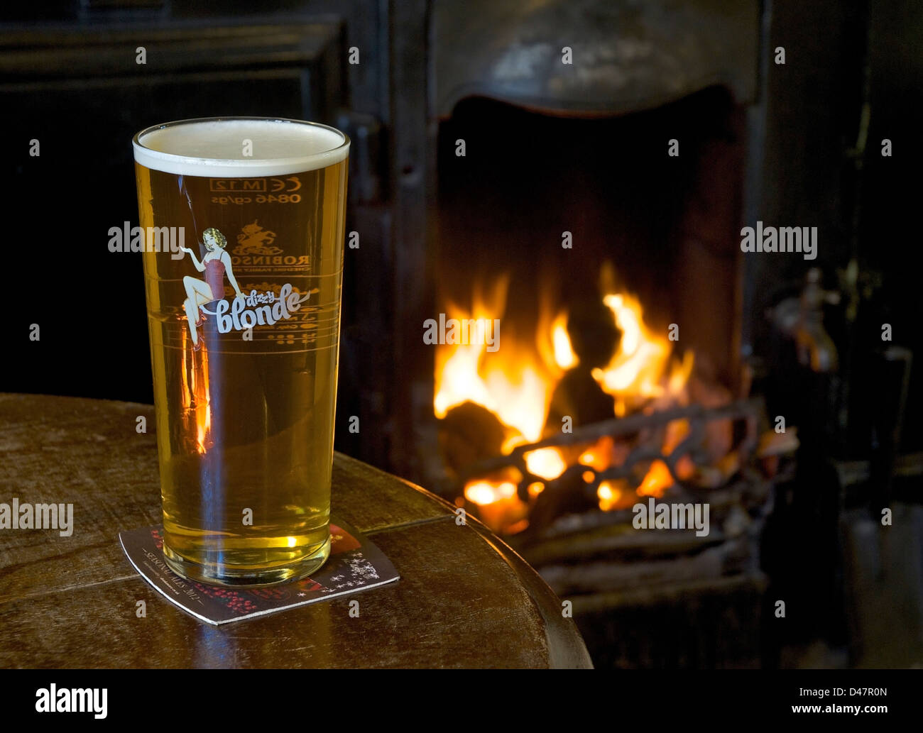 A pint of Dizzy Blonde beer on a pub table, with open fire in the background Stock Photo