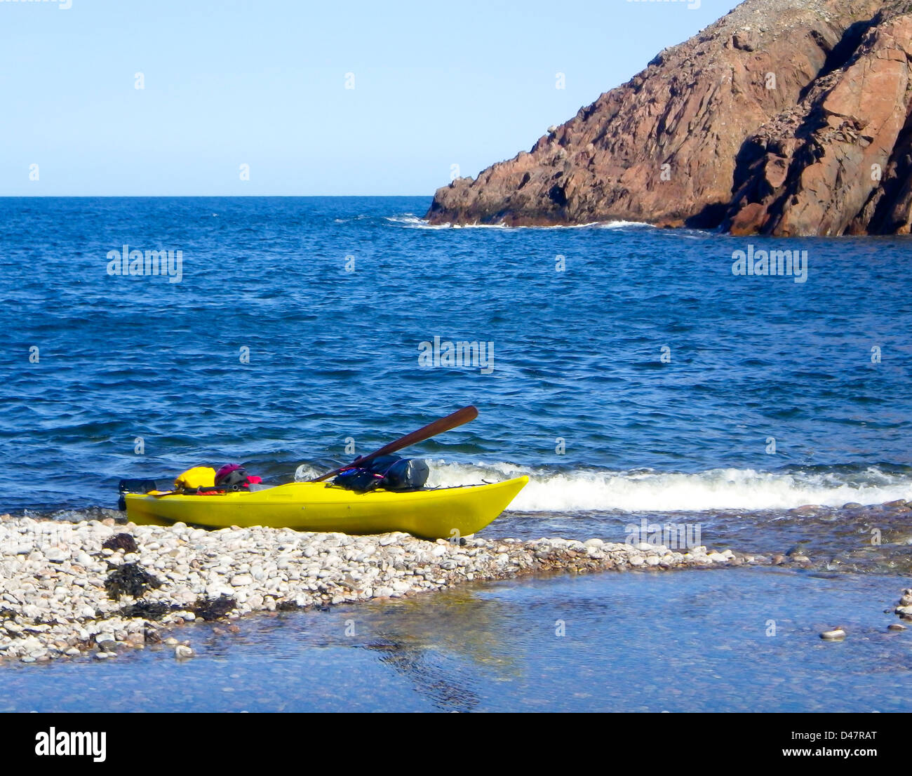 kayak well equipped and ready for expedition, anchored on a beach of Cape Breton,, Nova Scotia, Canada - Stock Image