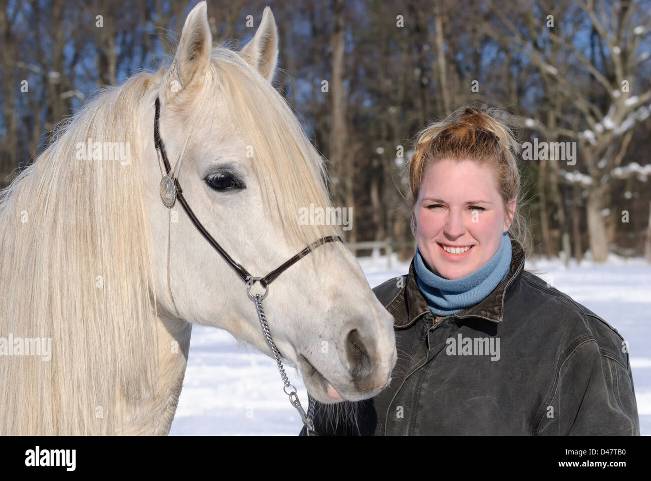 Woman and her white horse in outdoor winter snow portrait, a twenty-something blond and an Arabian stallion. - Stock Image