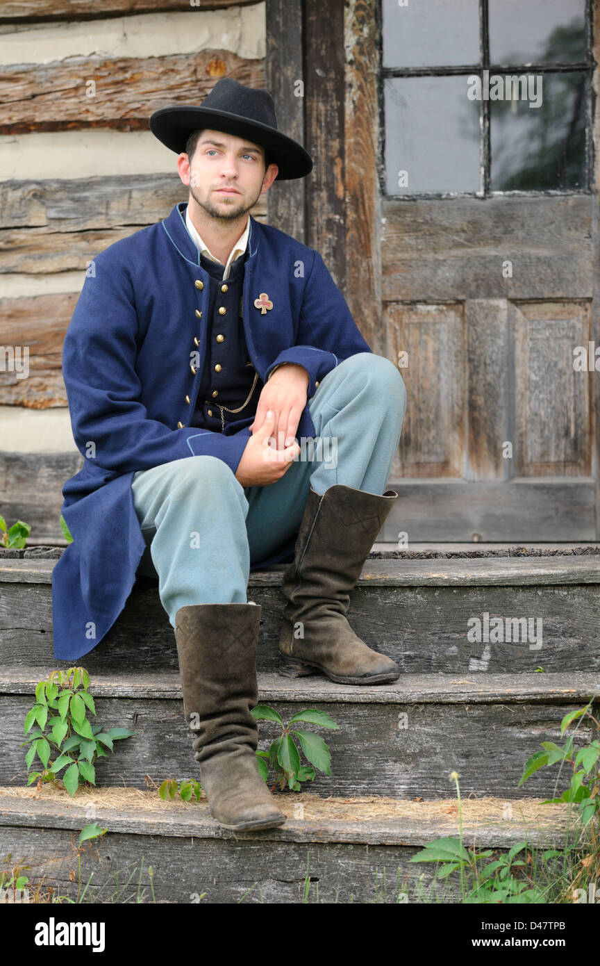Soldier sitting on log house steps, American Civil War Union infantry private reenactment portrayal. - Stock Image