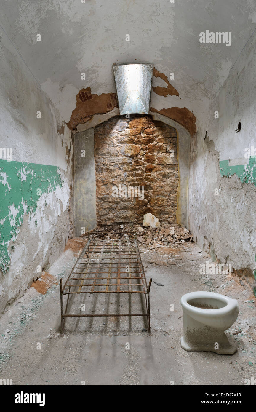 Abandoned prison cell with bed frame and toilet, Eastern State Penitentiary ruins, Philaelphia, PA, USA. - Stock Image