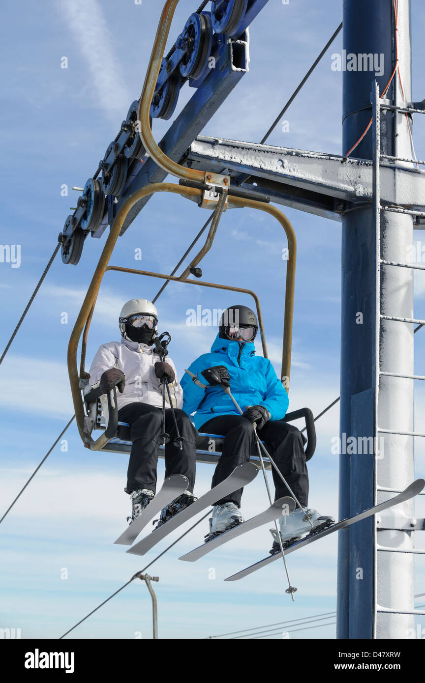 Two Skiers Riding Ski Lift Chair In Close Up, Man And Woman With Sunlight  And Fair Weather Sky Background, Copy Space.