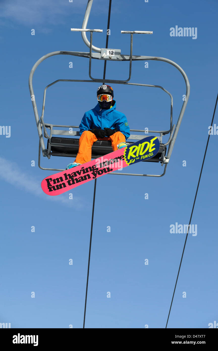 Snowboarder riding winter ski lift taken from below with colorful pink board with fun phrase. - Stock Image