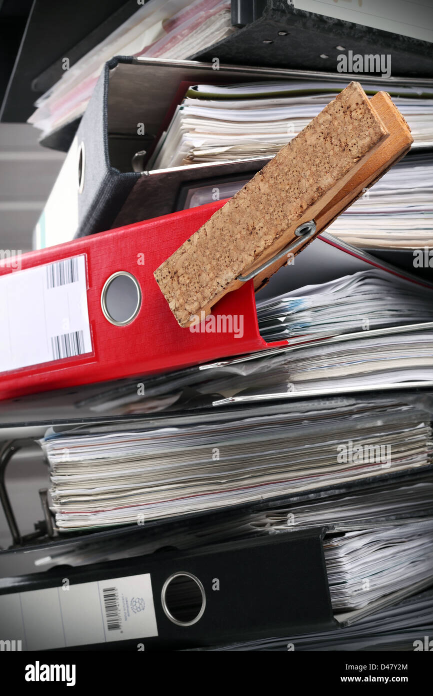A red folder in a tower of black ones. - Stock Image
