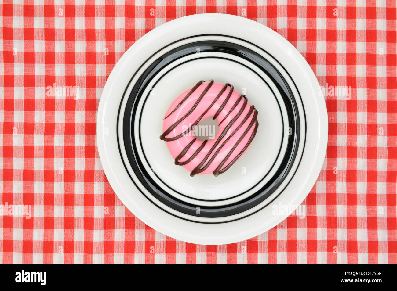 A donut with pink icing and drizzled chocolate, on a white plate which is placed on a red-and-white checkered tablecloth, - Stock Image