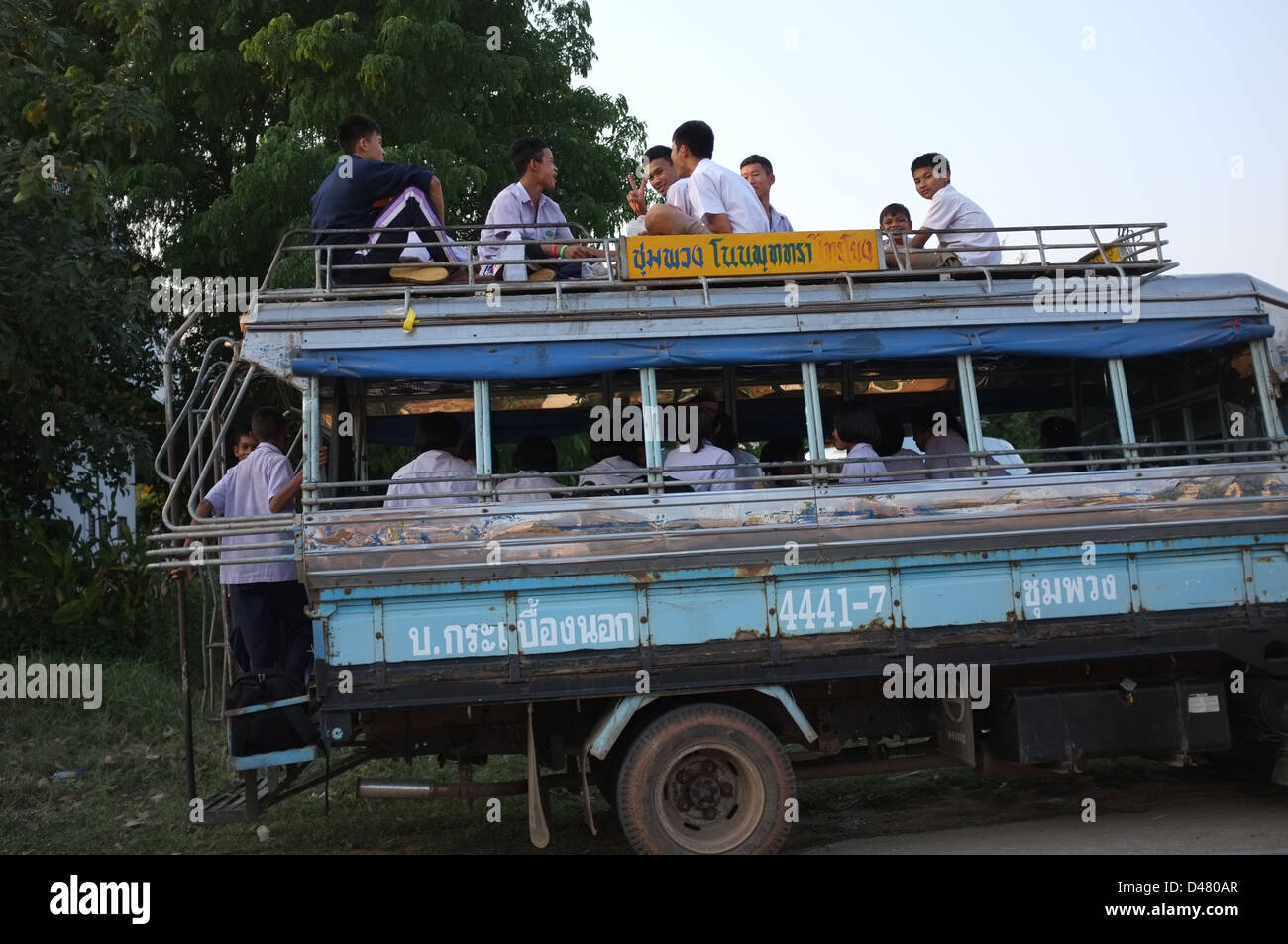 Thai schoolchildren ride a local bus as they return home after school. - Stock Image