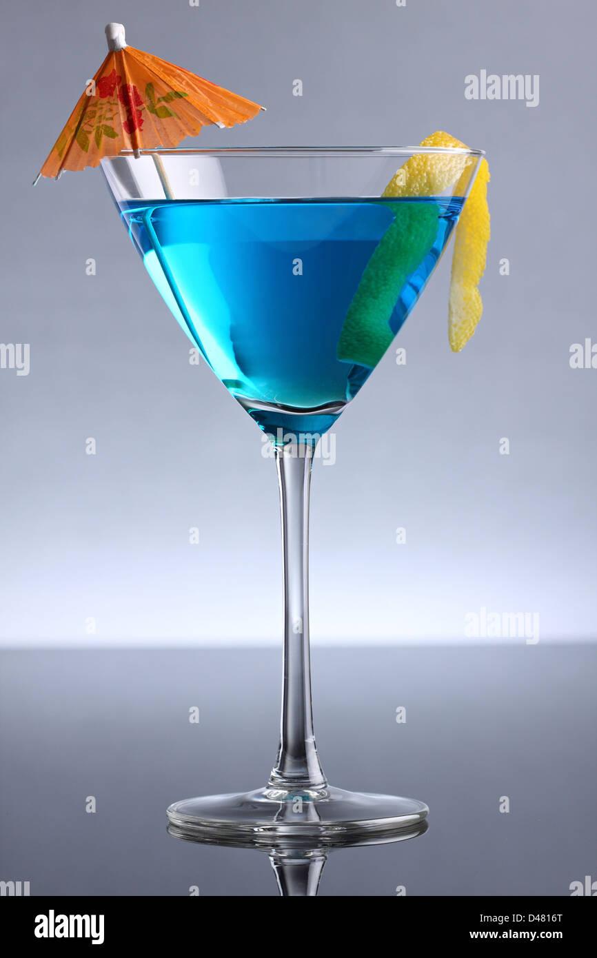 A blue cocktai with lemon and an umbrella. Stock Photo