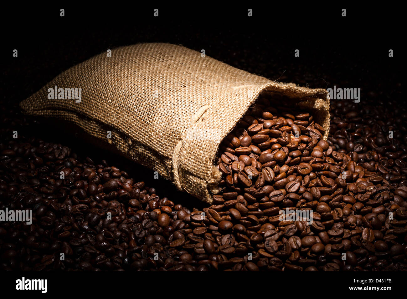 a spilled coffee bag in spotlight - Stock Image