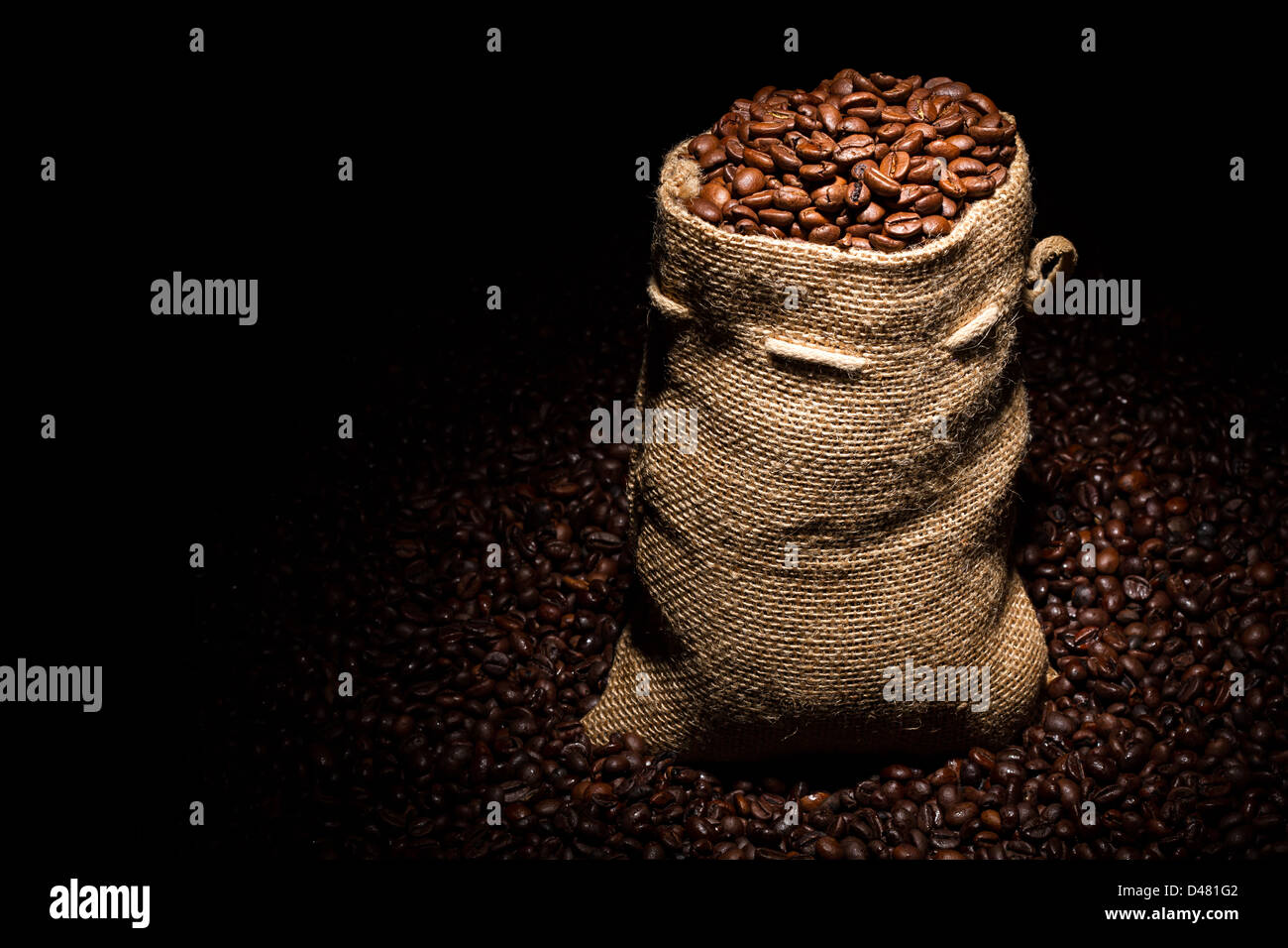 bag filled with coffee beans in spotlight - Stock Image