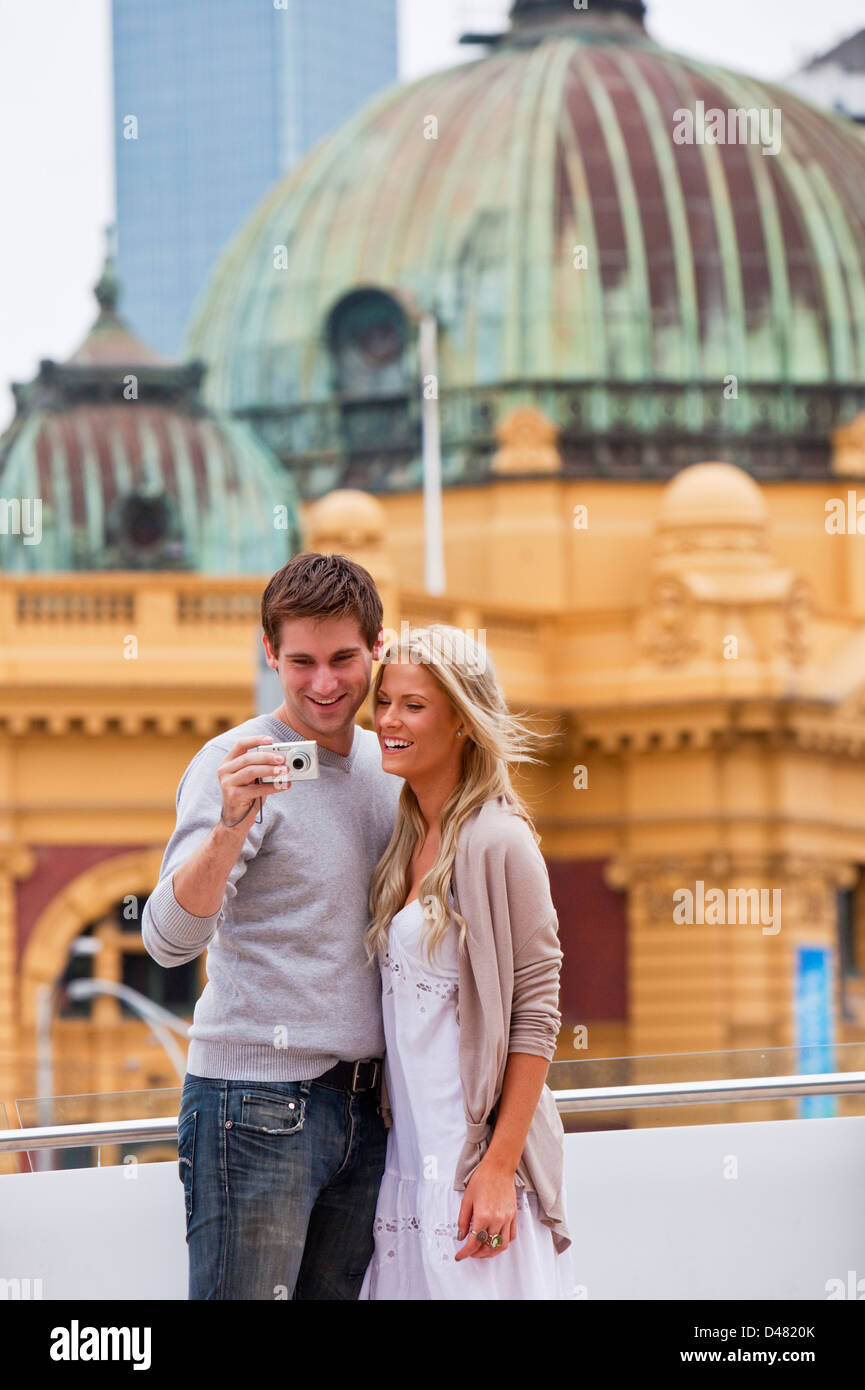 Young couple sightseeing in city, looking at pictures on camera. Federation Square, Melbourne, Victoria, Australia - Stock Image
