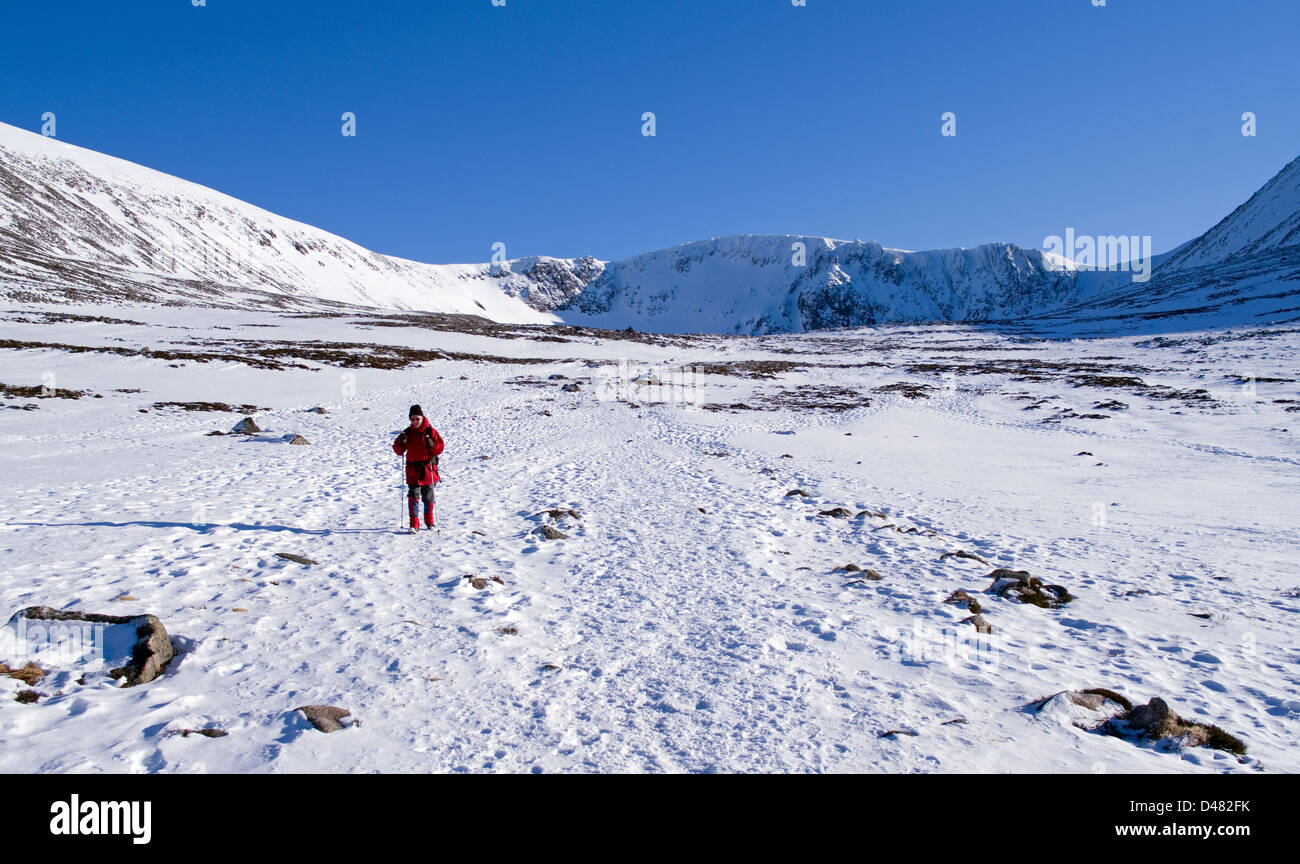 Hillwalker crossing the snowfield below Coire an t-Sneachda, the Cairngorms, Scottish Highlands, winter, Scotland - Stock Image