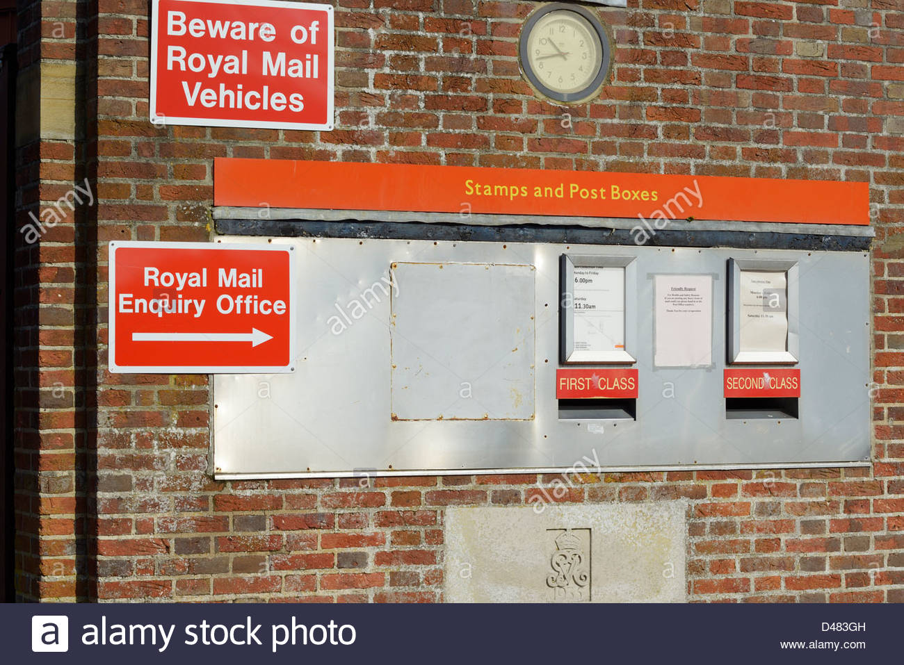 Post Office wall with postboxes, signs and clock, Blandford Forum, Dorset England UK - Stock Image