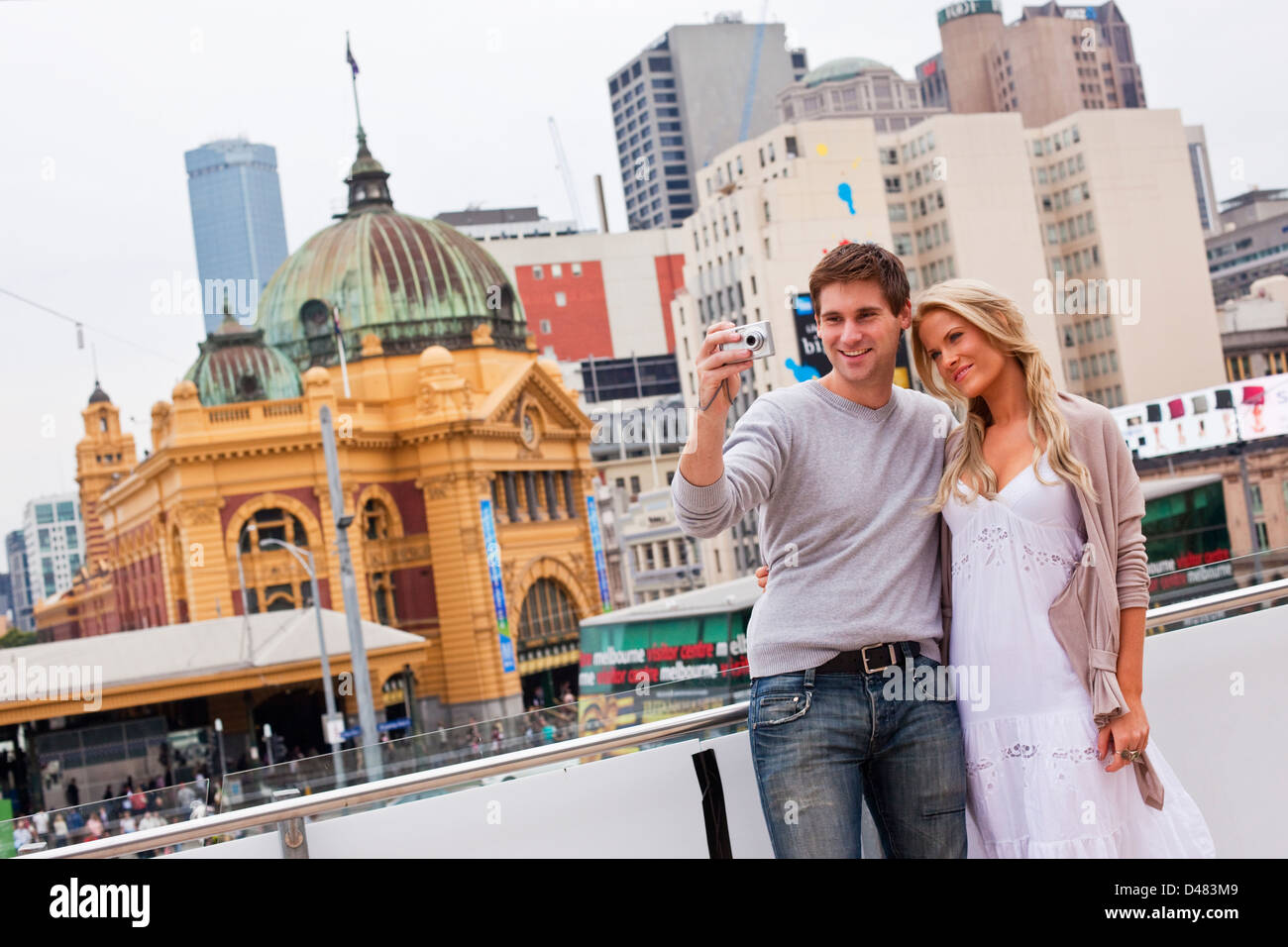 Young couple sightseeing in city, taking a picture. Federation Square, Melbourne, Victoria, Australia - Stock Image
