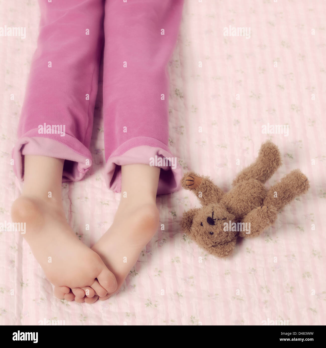 female feet in pink pyjamas with a teddy bear - Stock Image