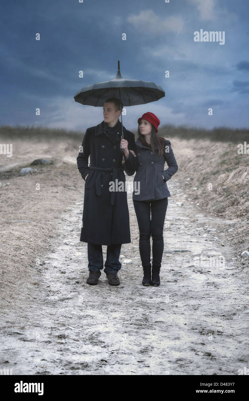 a couple is doing a walk in the rain - Stock Image