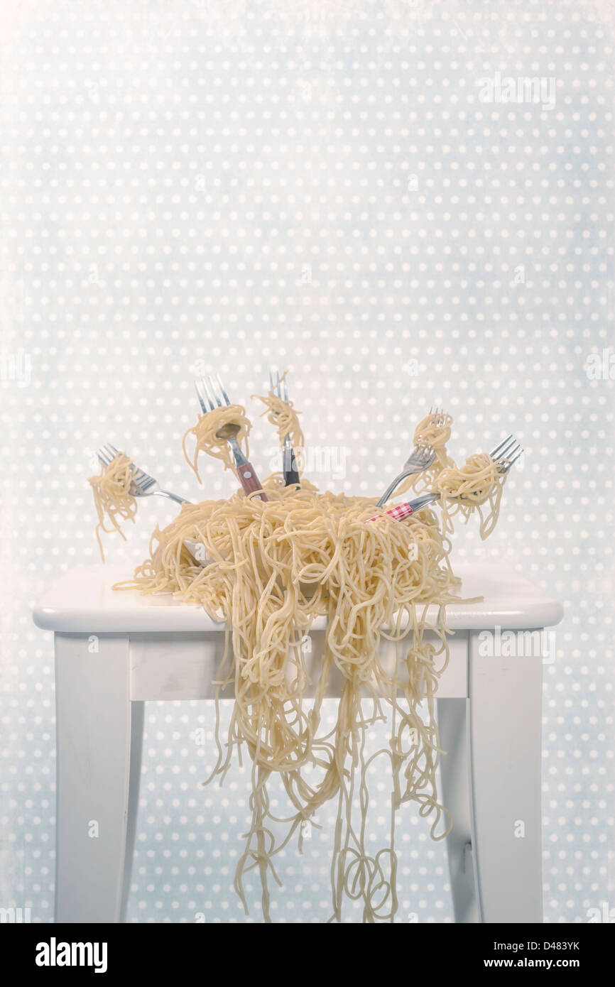 a plate full of spaghetti with five forks - Stock Image