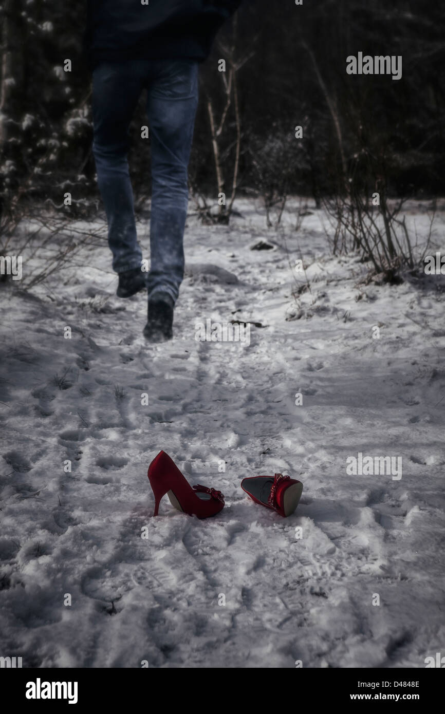 red high heels in snow, a man is running away - Stock Image