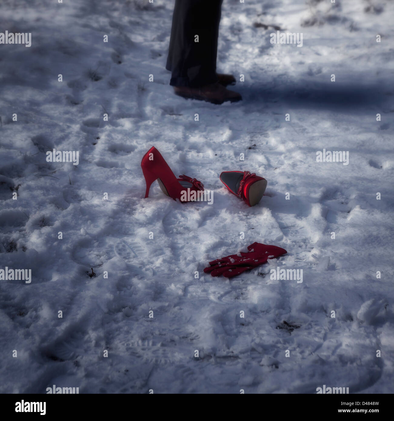 red high heels and a glove in snow, a man is standing beside - Stock Image