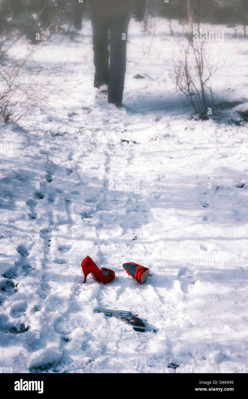 red high heels and a gun in snow, a man is walking away - Stock Image