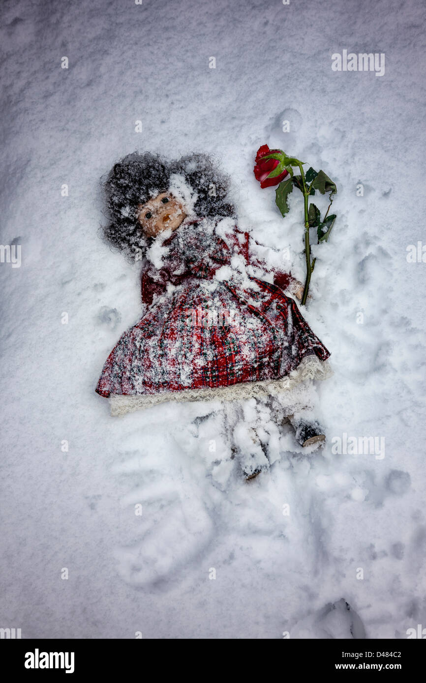 doll buried in snow with a red rose - Stock Image