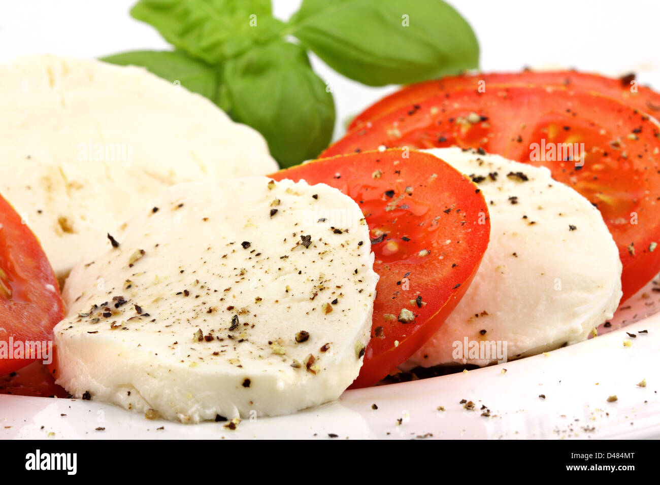 mozzarella and tomato slices with pepper and basilicas. - Stock Image