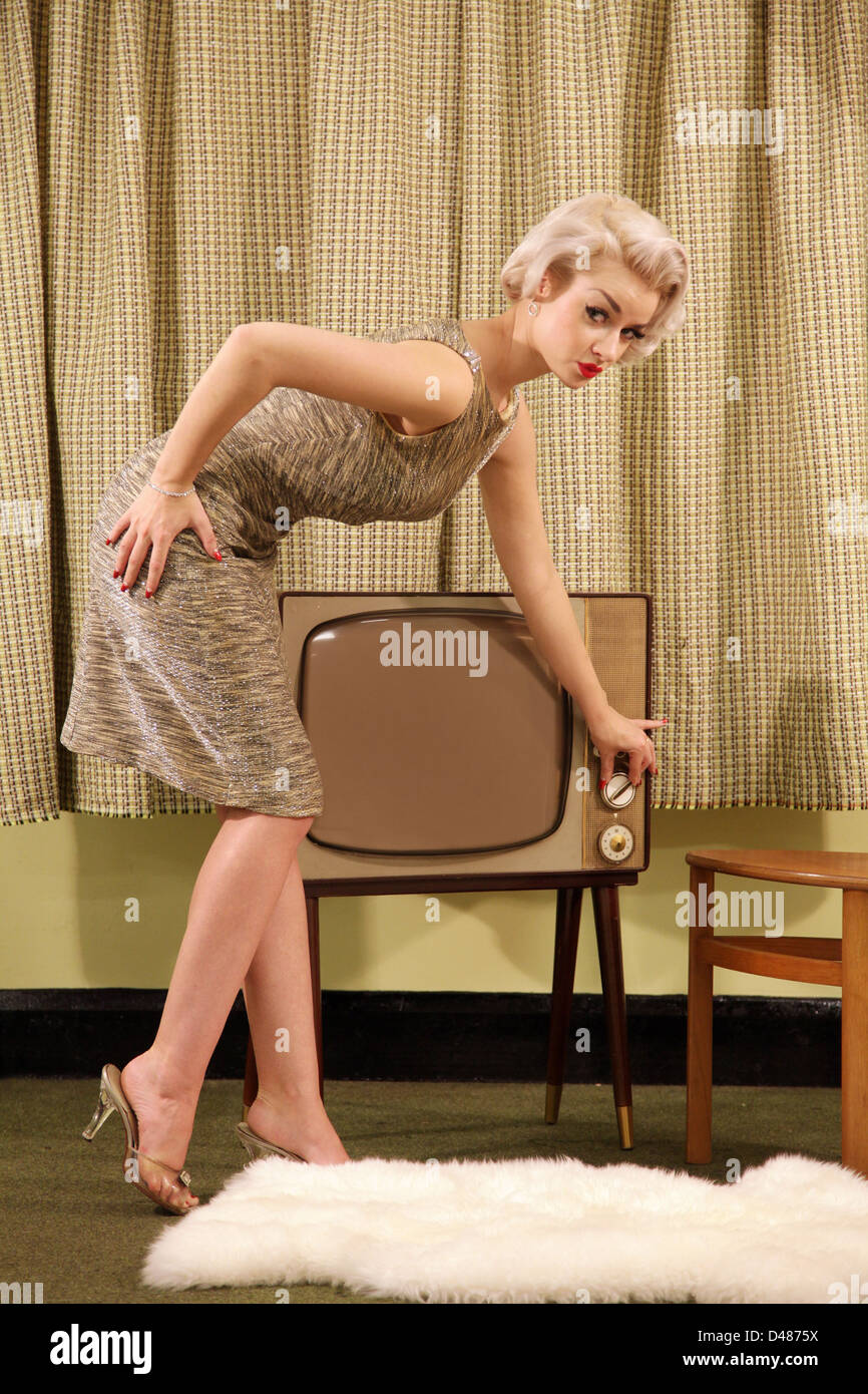 Woman adjusting channel knob of a vintage television set. - Stock Image
