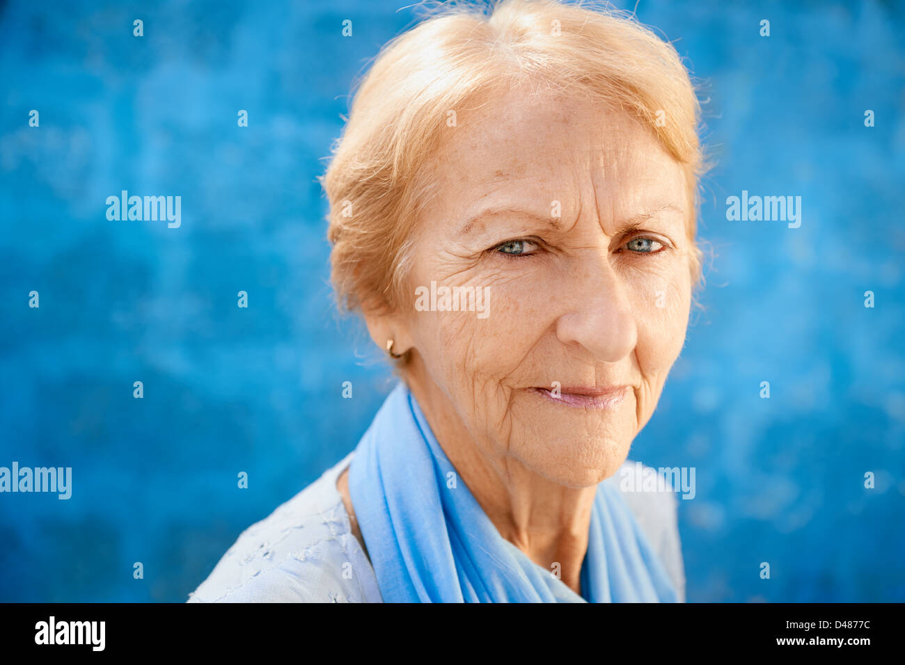 Senior people portrait, happy old blonde woman in blu clothes smiling and looking at camera against blue wall - Stock Image